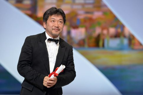 """Japanese director Hirokazu Kore-Eda poses on stage on May 26, 2013 after being awarded with the Prix du Jury (Jury's Prize) for the film """"Like Father, Like Son"""" during the closing ceremony of the 66th Cannes film festival in Cannes. AFP PHOTO / ALBERTO PIZZOLI"""