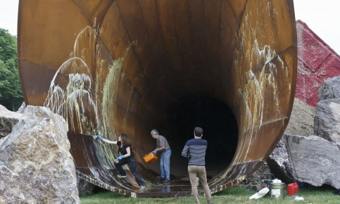 "Chateau de Versailles workers clean the sculpture ""Dirty Corners"" by British artist Anish Kappor after it was splattered with paint, in the gardens of the Chateau de Versailles outside Paris, France, Thursday, June 18, 2015. (AP Photo/Michel Euler)"